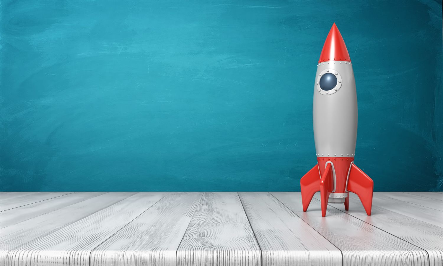 3d rendering of a red and silver realistic model of a retro rocket stands on a wooden desk on a blue background. Science fair. Goals and dreams. Fly in space.